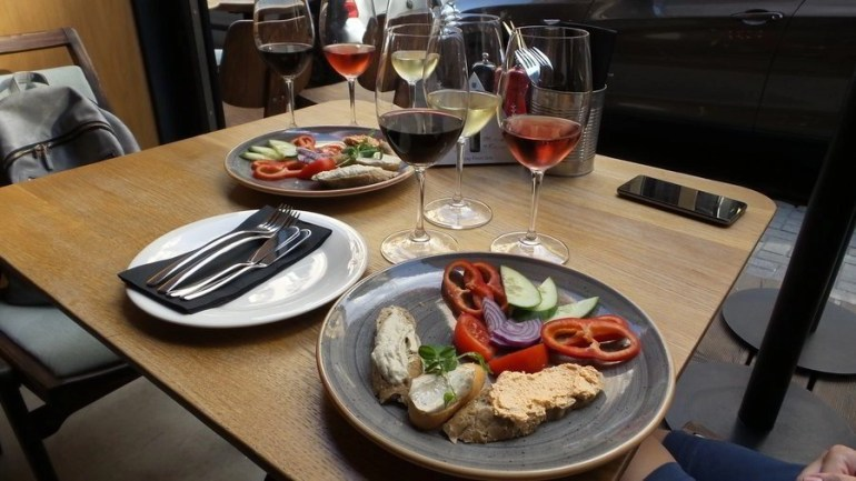 Plates of tapas with glass of wine for tasting in Budapest.