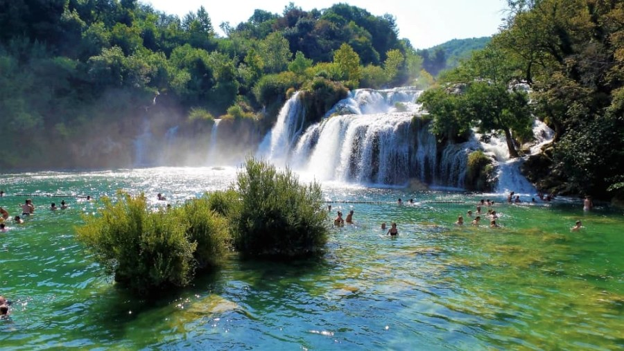 People swimming at the waterfalls in the Krka national park in Croatia.
