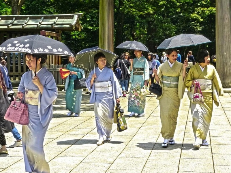 Ladies in Kimono outfit holding umbrellas walking down a pathway.
