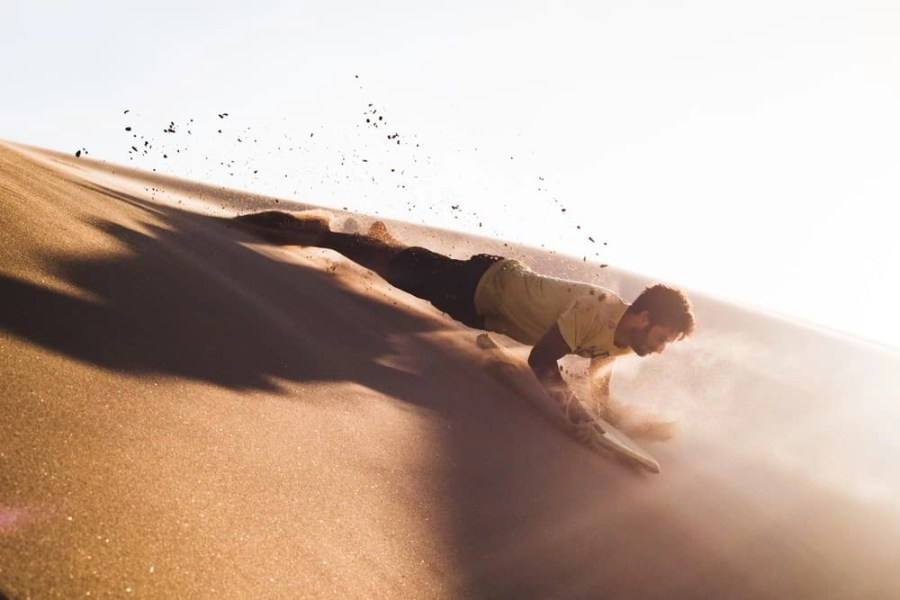 A man going down a hill of sand or a desert.