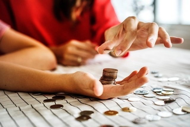 A woman stacking coins in someone else's hand.