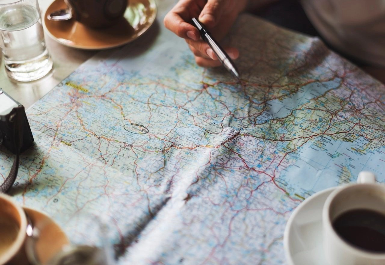 A pen in a hand over a paper map on a table.