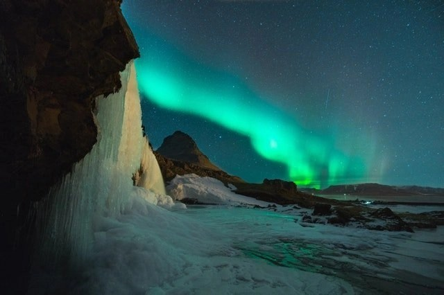 The aurora over a mountain at night.
