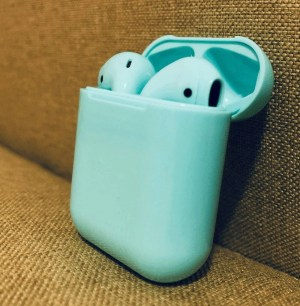 Green wireless earpods in charging case on textured background.