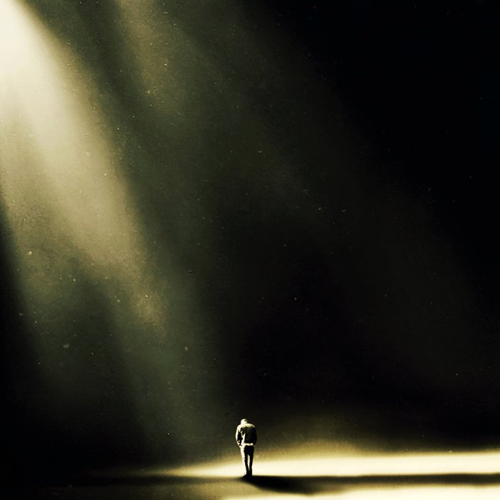 uomo raggiunto da un raggio di luce nel buio