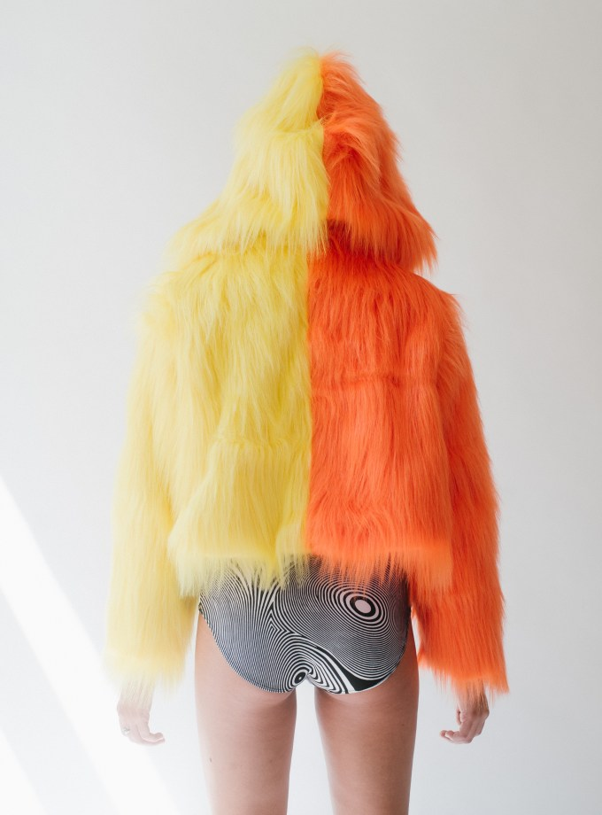orange and yellow faux fur jacket on girl with bathing suit bottoms