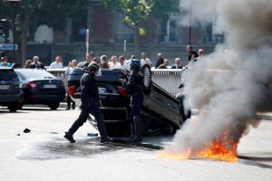French riot police stand next to an overturned car as striking French taxi drivers demonstrate at the Porte Maillot to block the traffic on the Paris ring road during a national protest against car-sharing service Uber, in Paris, France, June 25, 2015. French taxi drivers stepped up protests against U.S. online cab service UberPOP on Thursday, blocking road access to airports and train stations in Paris and other cities. REUTERS/Charles Platiau  TPX IMAGES OF THE DAY