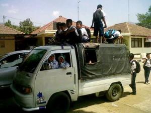 MEMBAHAYAKAN: Sejumlah siswa dari Desa Ibun turun dari angkutan bak terbuka yang dilengkapi terpal saat tiba di kawasan Kecamatan Ibun, baru-baru ini. Para siswa kerap bertaruh nyawa agar tidak terlambat sekolah dan minimnya sarana transportasi di kawasan tersebut.