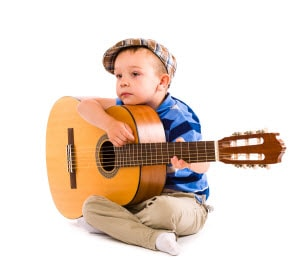Young boy taking guitar chords lesson