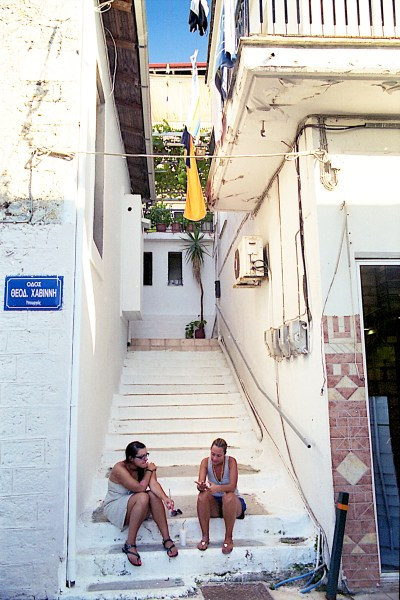 Two girls sitting on the stairs of a small alley