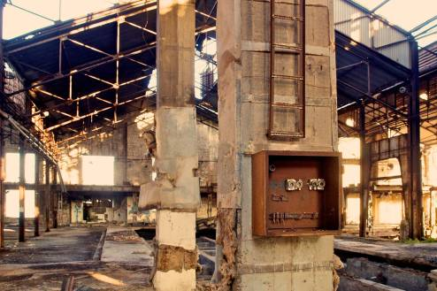 A destroyed electrical panel in a ruined factory.