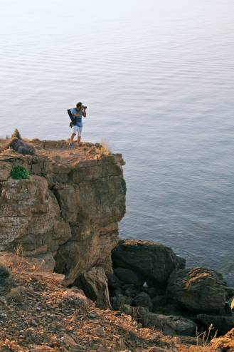A landscape photographer shooting on top of a rock by the sea.