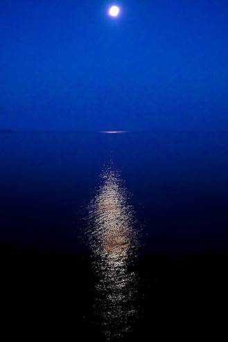 An almost full moon reflecting on the calm sea.