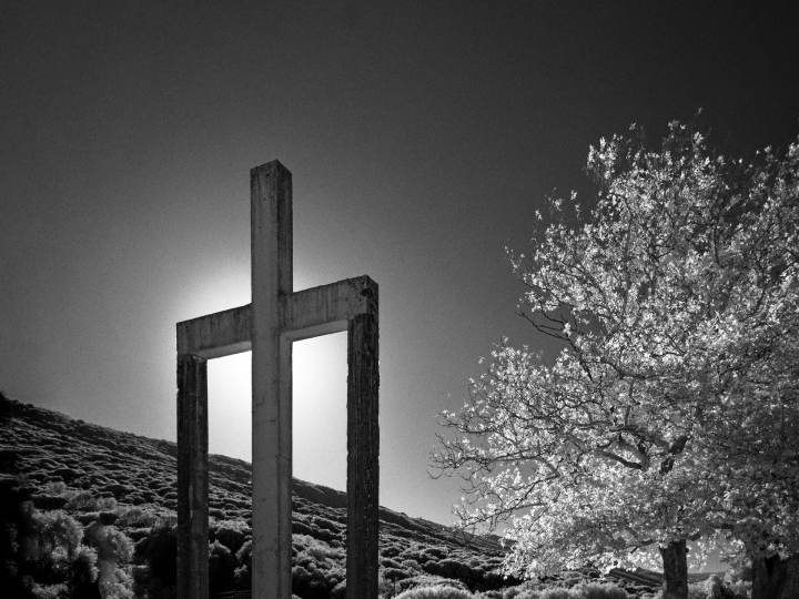 "A concrete cross hides the sun in this black and white photo. The supports for the two arms make a strange design, almost like a peculiar ""Π""."