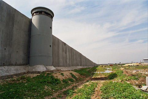 The Wall around Qalqiliya. A twenty-five foot high concrete cage cuts residents off from their agricultural land, necessary for their survival, and prevents you from traveling even 5 minutes out of the City. A single gate, open at the whims of the occupying army, controls 100,000 residents.