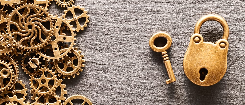 Various metal cogwheels and gear wheels with lock and key over slate background