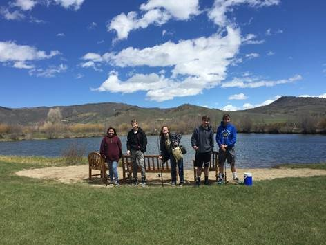 Five students at a lake with fishing poles