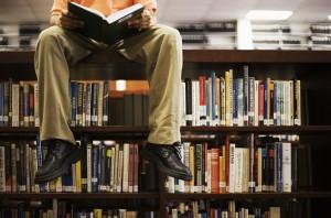 Hombre leyendo desde el estante