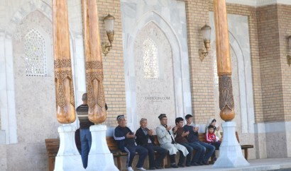 A family in dua beside Imam Bukhari's tomb