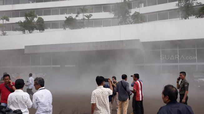 Pegawai dan pengunjung berada diluar Gedung Nusantara III DPR RI yang dipenuhi asap, Jakarta, Senin (24/2). [Suara.com/Novian]