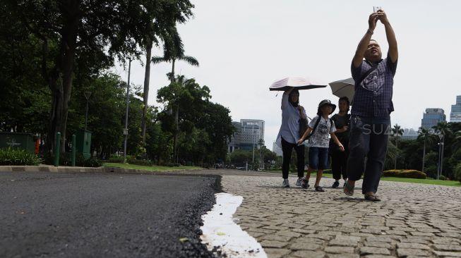 Sejumlah pengunjung melintas di samping aspal uji coba lintasan Formula E di kawasan Monumen Nasional (Monas), Jakarta, Sabtu (22/2). [Suara.com/Angga Budhiyanto]