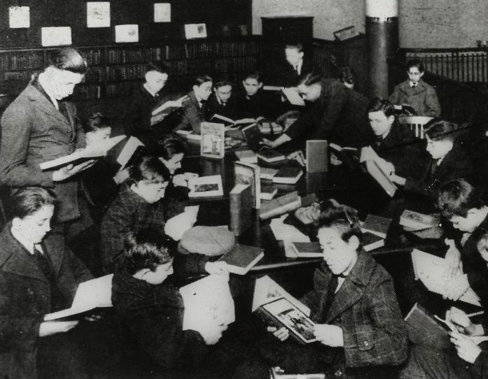Work with schools after a book talk, showing boys gathered from New York Public Library