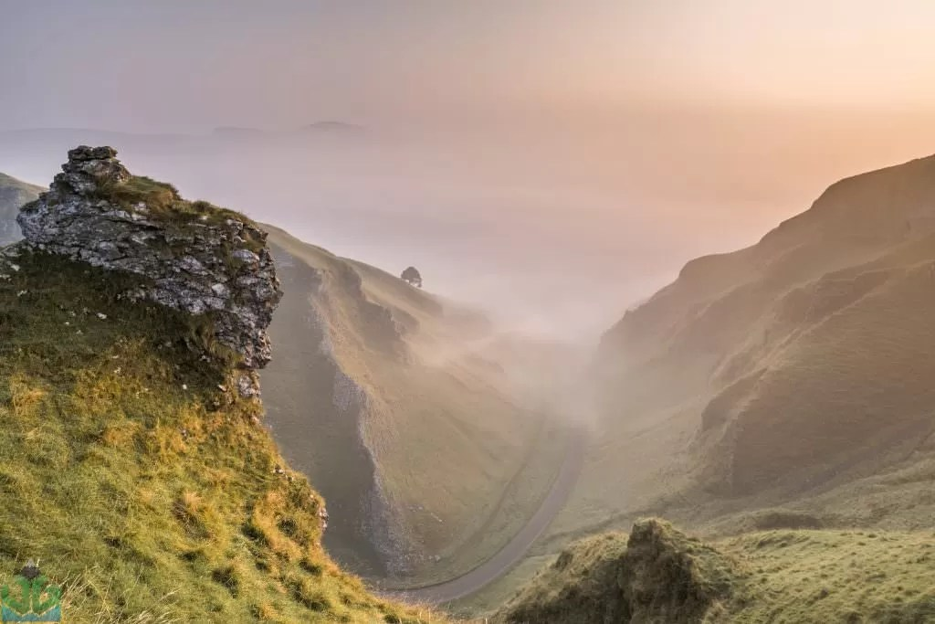 A hazy sunrise from the top of Winnats Pass with the huge drop below. The Hope Valley swamped in a thick fog hiding all but only the highest of hills.