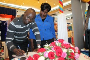 Kenya Publishers Association Chairman David Waweru signs the visitors book as KLB Managing Director Mrs. Eve Obara looks on.