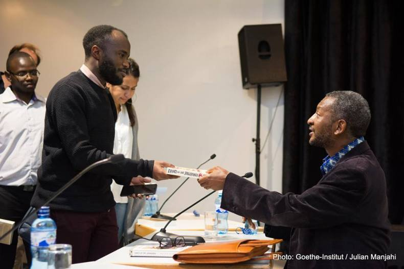 Peter Kimani signs book for an audience member. Photo/Julian Manjahi