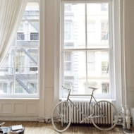 Photograph of the Apartment by the line. You can see big white windows, a wooden floor, white curtains and a white wall. A bicycle is standing in front of one window.