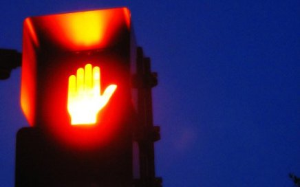 A lit red hand of a crosswalk sign.