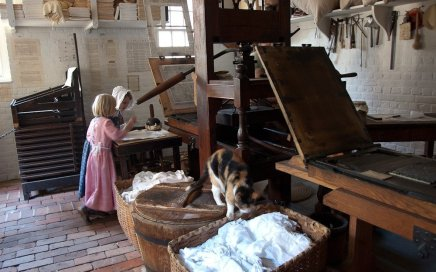 Image: young girls in period costume at historic printing press