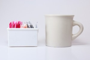 colored sweetener packets in a white ceramic holder with a white coffee mug next to it