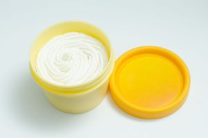 open yellow cream jar with white lotion isolated on white background. skin care product package. opaque beauty cream container. place for logo. cosmetics, lotion