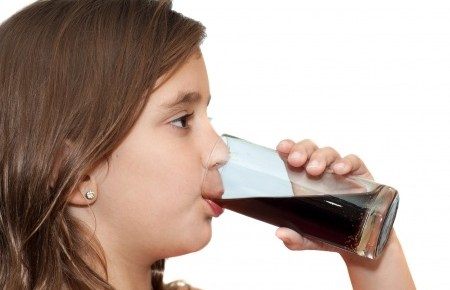 a young girl drinking a glass of cola