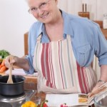 a smiling grandma stirring a pot in the kitchen