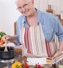 a smiling grandma stirring a pot in the kitchen