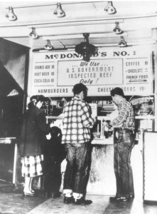 a black and white picture of 2 men at a food counter
