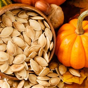 Close up image of toasted, salted pumpkin seeds spilling from a wooden bowl, accented with nuts and a small pumpkin