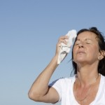 A woman wiping the sweat off her face with a white towel