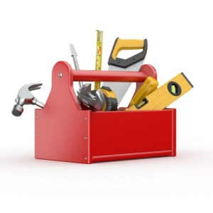 a red wooden tool box with saws, hammers, and tools in it