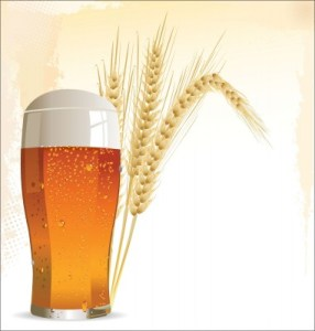 a glass of beer with 2 wheat shafts behind the glass