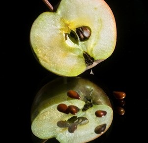 a green aple cut in half with the seeds falling on a table