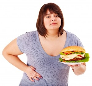 a fat girl holding a plate of food and holding her side in pain