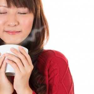 an asian girl in a red dress drinking a white cup of hot tea