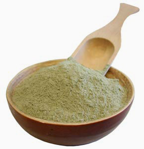 a wooden bowl with powdered French Green Clay and a wooden spoon in the bowl.a wooden