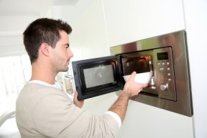 a young man using a microwave