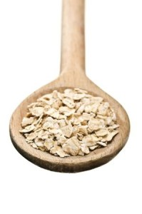 raw oatmeal in a wooden spoon