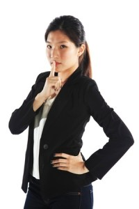 an Asian girl with her finger over her lips