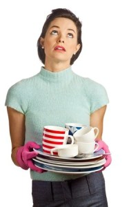 tired white woman holding a stack of dirty dishes iwth dish gloves on